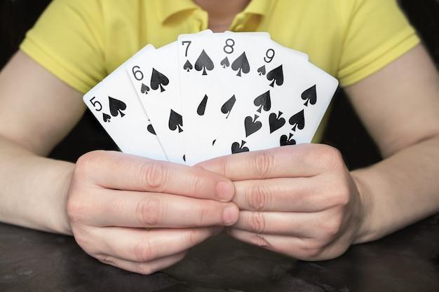 Close-up van handen met vijf kaarten met een poker straight flush van een rij schoppen. gokken, pokersporten