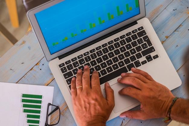 Close-up van handen schrijven en werken met laptop op kantoor op een blauwe houten tafel met statistieken en grafieken