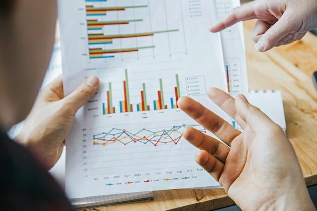 Close-up van handen. twee jonge ondernemers analyseren investeringsgrafieken.