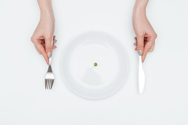 Close-up van handen van een jonge vrouw die een kleine groene erwt eet met mes en vork