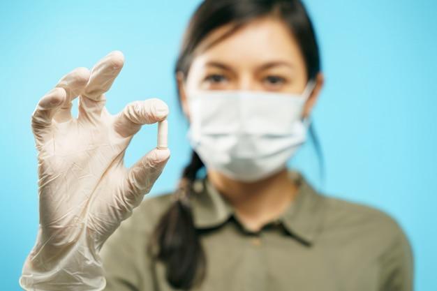 Close-up van handen van een jonge vrouw in een beschermend medisch masker en handschoenen die een capsule of pil op blauw houden