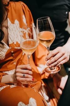 Close-up van handen van een paar met glazen champagne.