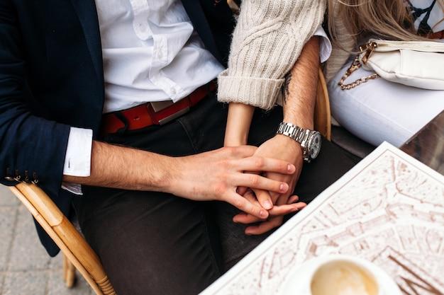 Close-up van handen van jong paar in liefde die en pret stellen openlucht in koffie