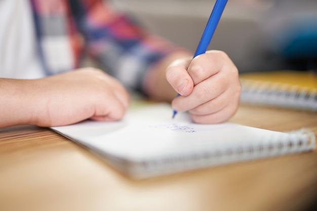 Close up van handen van latijns-amerikaanse schooljongen die aantekeningen maakt tijdens online les. kind studeert thuis. online onderwijs, technologie, thuisonderwijs concept