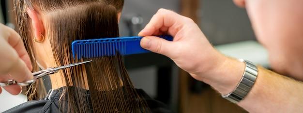 Close up van handen van mannelijke kapper knippen lang haar van jonge vrouw met schaar en kam in de salon