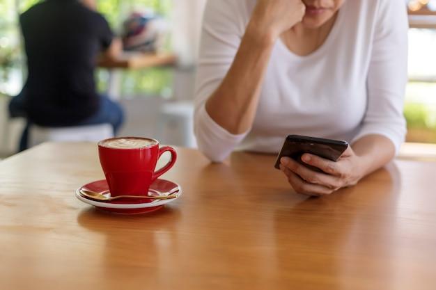 Close-up van handen van mooie jonge vrouw met mobiele, smartphone zittend in café. zachte focus.