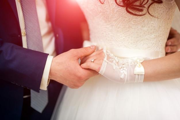 Close-up van handen van romantisch paar die tijdens huwelijksceremonie samenhouden.