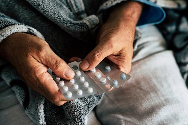 Close-up van handen van senior man die een kussen neemt of kiest om zijn koorts te genezen en gezond en niet ziek te zijn