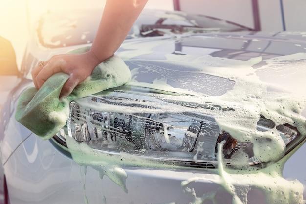 Close up van handen wassen auto met spons en zeepschuim