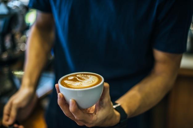 Close-up van handenbarista maakt de verf van de latte koffiekunst