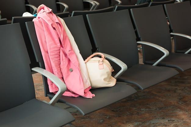 Close-up van handtas en jas op de stoel op de luchthaven. reizen, vakantie, bedrijfsconcept.