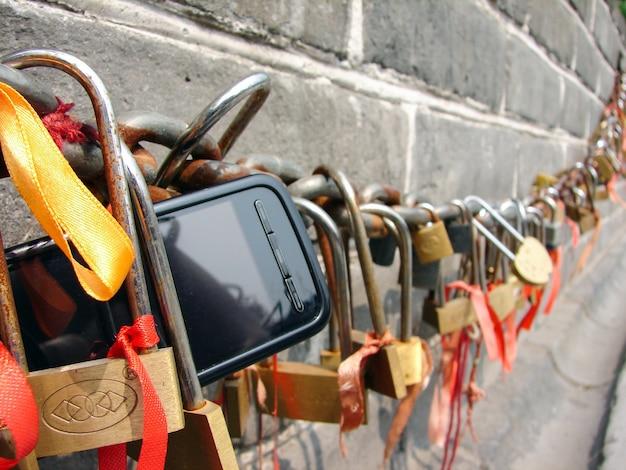Close up van hangsloten en mobiele telefoon aan een ketting. de chinese muur. van