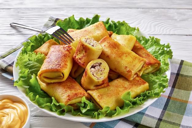 Close-up van hartige crêpe broodjes met gemalen kippenvlees en champignons vulling geserveerd op een bedje van verse slablaadjes op een witte plaat