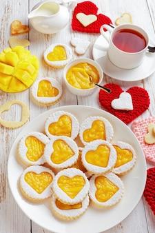 Close-up van hartvormige linzer koekjes met mangocam op een witte plaat op een tafel met gebreide hartvormige servetten. een kopje thee, gesneden mango en een kruik met room op tafel, verticale weergave