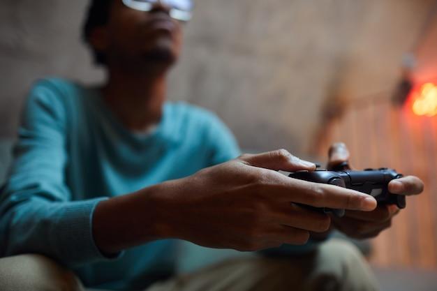 Close-up van hedendaagse afro-amerikaanse man met gamepad-controller tijdens het spelen van videogames