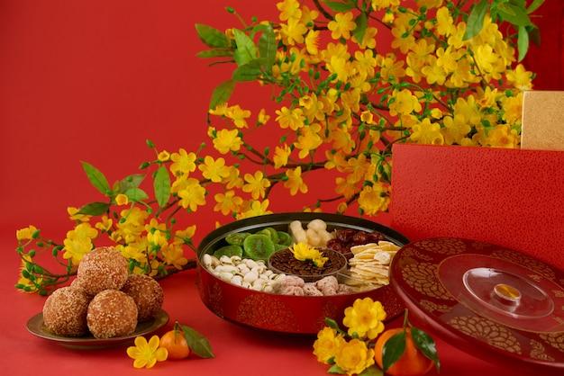 Close-up van heerlijk nieuwjaarvoedsel op een gediende lijst, rode achtergrond