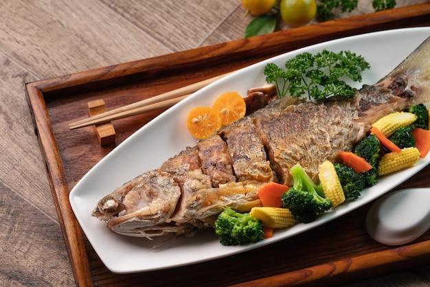Close up van heerlijke gebakken visschotel in een witte plaat met groente op een houten tafel.