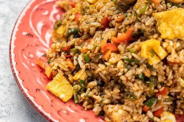 Close-up van heerlijke gekookte rijst met groenten en saus in een plaat op tafel