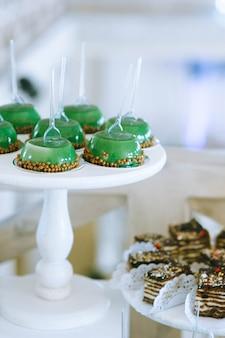 Close up van heerlijke groene gelei taarten op houten dienbladen op tafel op zoete bruiloft buffet. snoepreep. verscheidenheid aan mooie porties snoep.