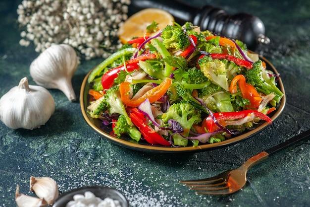 Close-up van heerlijke groentesalade met verschillende ingrediënten, knoflook, vork, zout, zwarte hamer op donkere achtergrond