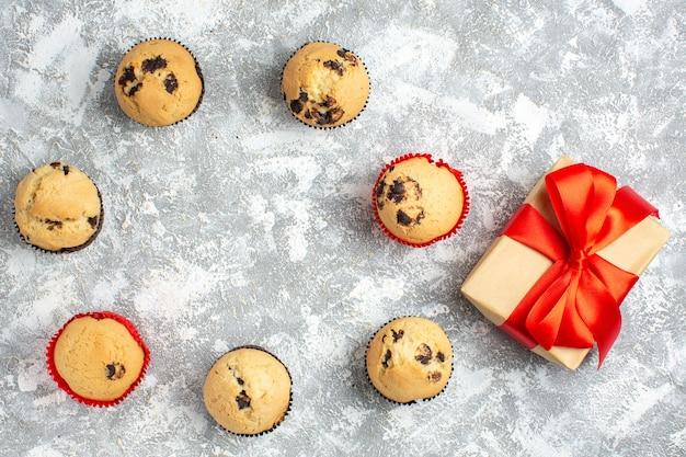 Close-up van heerlijke kleine cupcakes met chocolade en cadeau met rood lint op ijsoppervlak