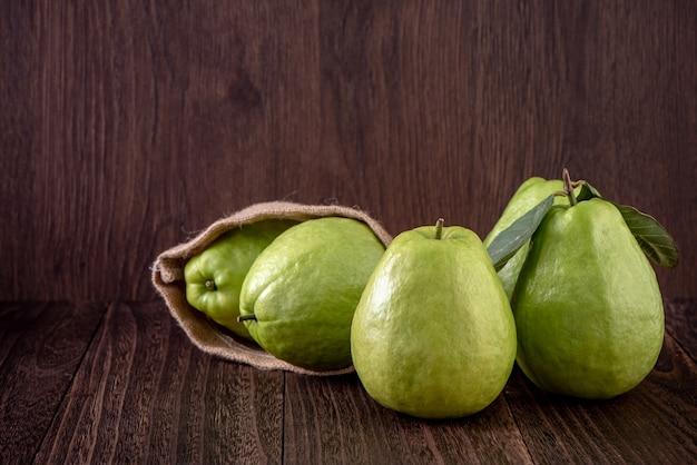 Close up van heerlijke mooie guave set met verse groene bladeren geïsoleerd op houten tafel