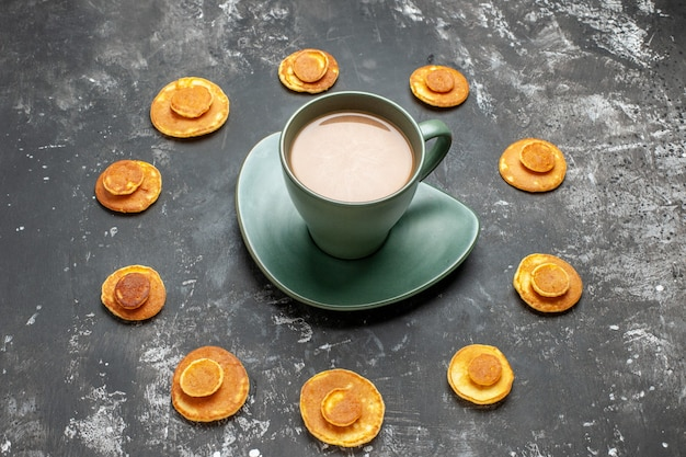 Close-up van heerlijke pannenkoek rond een kopje koffie op grijs