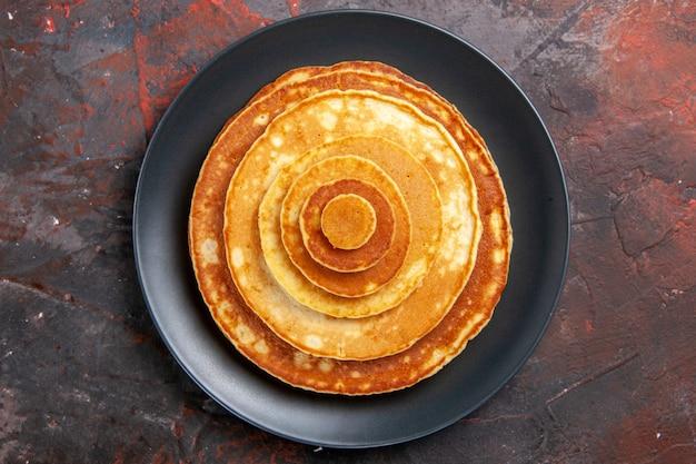 Close-up van heerlijke pannenkoeken voor het ontbijt in een zwarte plaat