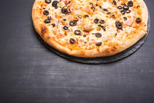 Close-up van heerlijke pizza op leisteen over de donkere achtergrond