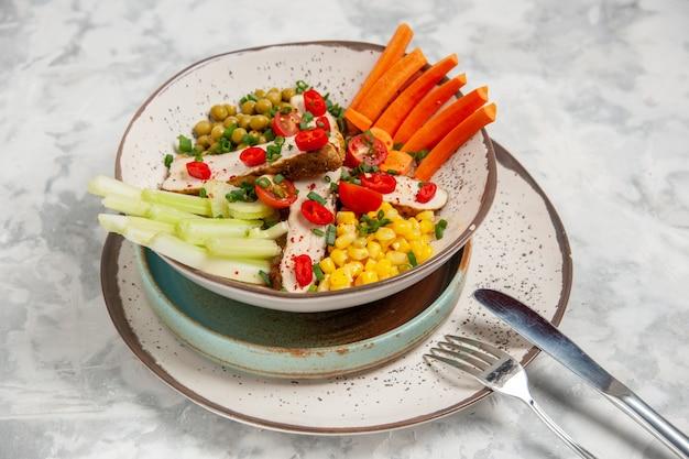 Close-up van heerlijke salade met verschillende ingrediënten op een bord op dienbladen en bestek op een wit oppervlak met vrije ruimte