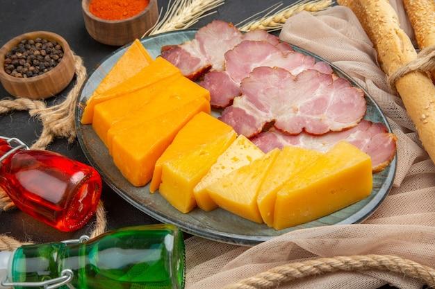 Close-up van heerlijke snacks gevallen flessen paprika's op handdoek en touw op een zwarte achtergrond