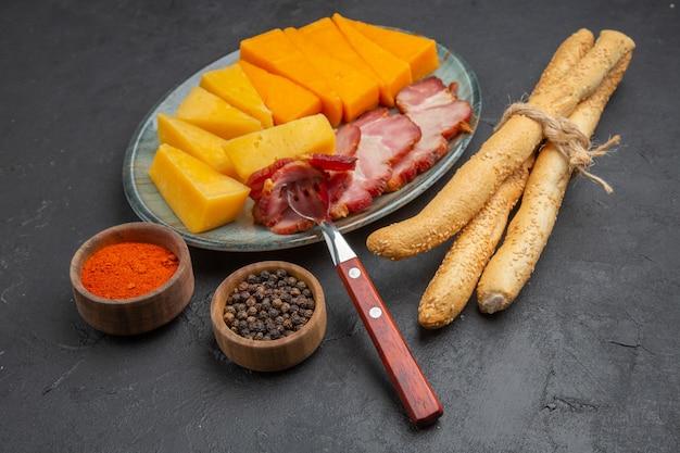 Close-up van heerlijke worst en kaasplak op een blauwe plaat paprika's op een donkere achtergrond