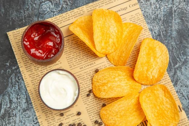 Close-up van heerlijke zelfgemaakte chips en peper kom mayonaise ketchup op krant op grijze tafel