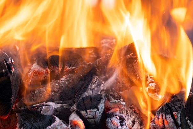 Close-up van helder brandende houten logboeken met gele hete vlammen van vuur 's nachts.