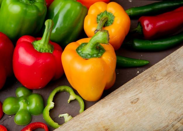 Close-up van hele en gesneden paprika's met snijplank