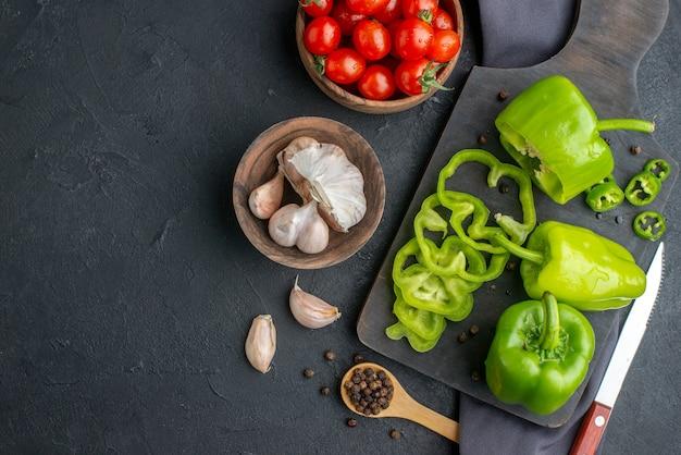 Close-up van hele gesneden gehakte groene paprika's op houten snijplank tomaten in kom knoflook op donkere kleur handdoek op zwart oppervlak