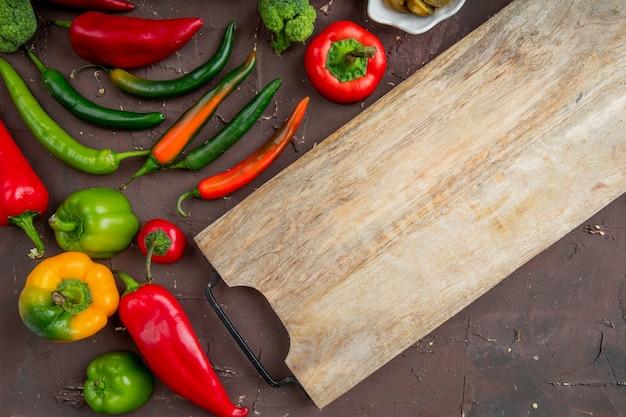 Close-up van hele paprika's, broccoli en snijplank