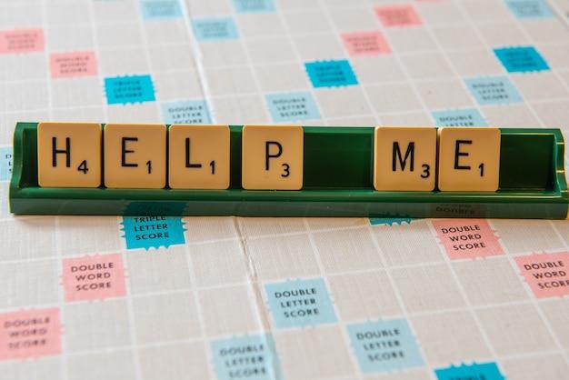 Close-up van help me geschreven op een scrambling board onder de lichten