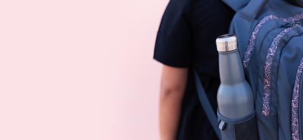 Close-up van herbruikbare, stalen thermo eco waterfles van blauwe kleur in zak van rugzak. pastel roze achtergrond. school tijd concept. wees plasticvrij.