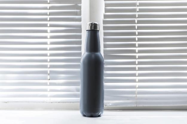 Close-up van herbruikbare, stalen thermo-waterfles op achtergrond van venster met jaloezie.