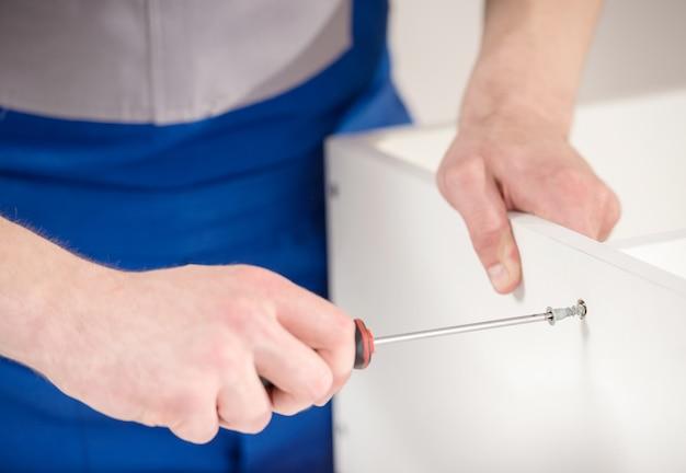 Close-up van hersteller die binnenland van reparatiehulpmiddelen thuis gebruiken.