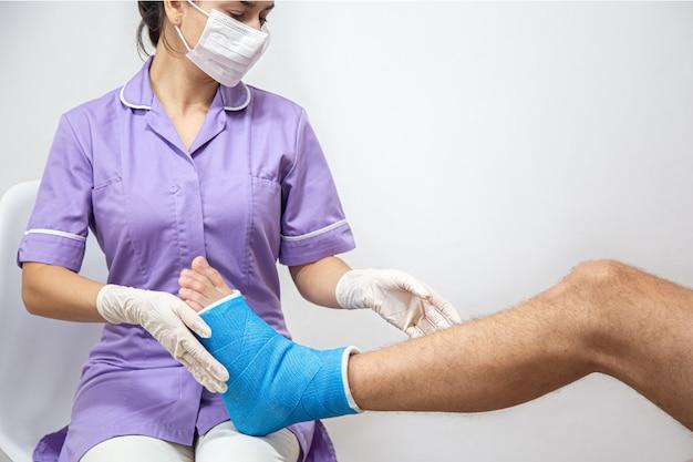 Close-up van het been van een man in het gips en een blauwe spalk na verband in een ziekenhuis.