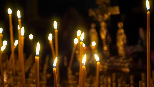 Close-up van het branden van waskaarsen tegen de achtergrond van een wazig kruisbeeld in een christelijke tempel.