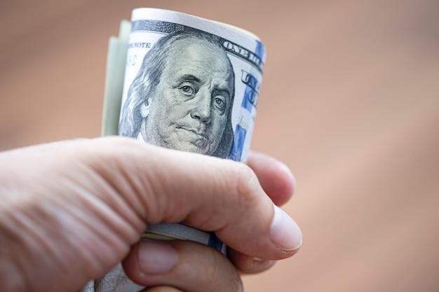 Close-up van het broodje van de handholding van amerikaanse dollarbankbiljet voor het betalen van iemand
