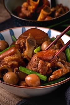 Close-up van het eten van taiwanees voedsel varkensvlees knokkel in een kom met stokjes op rustieke tafel