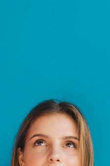 Close-up van het gezicht die van de jonge vrouw omhoog tegen blauwe achtergrond kijkt