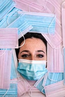 Close-up van het gezicht van een blanke vrouw met een masker op omgeven door blauwe en roze maskers. dit is een weerspiegeling van de realiteit van de wereld als gevolg van de pandemie.