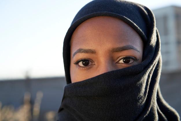Close-up van het gezicht van een jong moslimmeisje met hijab die de camera bekijkt.