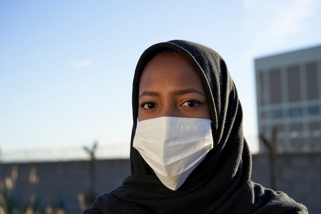 Close-up van het gezicht van een jong moslimmeisje met hijab en masker die de camera bekijken.