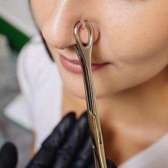 Close-up van het gezicht van een jonge vrouw met piercing die aan haar neus hangt.